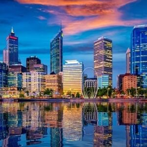 A picture of the Perth Skyline, taken from the harbour at sunset. The skyscrapers and larg public sculpture are reflected in the water.