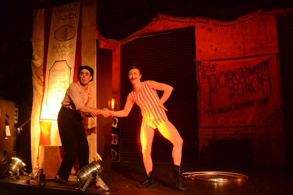 Two vaudeville characters on stage shake hands. One is in trousers and braces, the other a comical vintage swimming costume