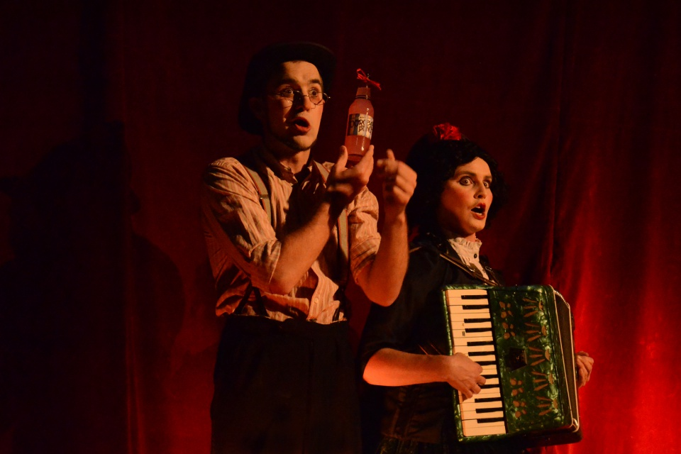 Two performers on stage. A male performer is holding a medicine bottle with bow tied arounf the top, accompanied by a female performer playing an accordion piano.