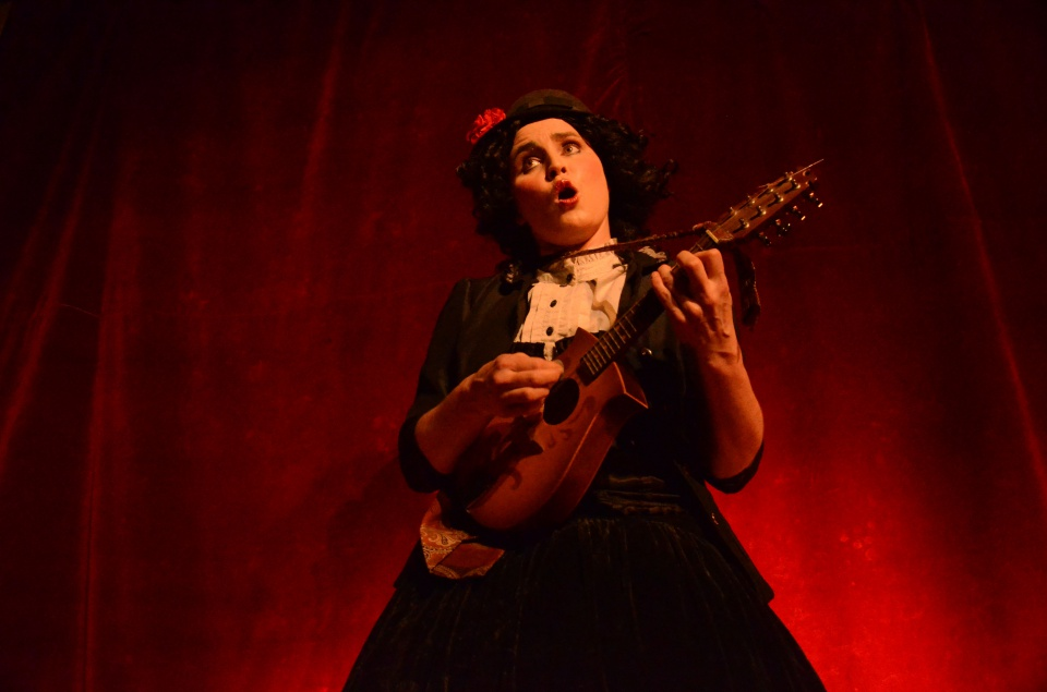 A woman in period costume with a flower in her hair sings while strumming an acoustic guitar