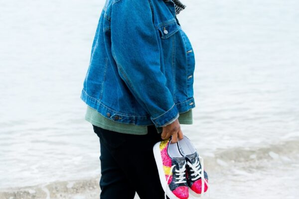 An indigenous woman with grey hair walks along the beach at the waters' edge. She is waring a denim jacket and holding her sneakers in one hand