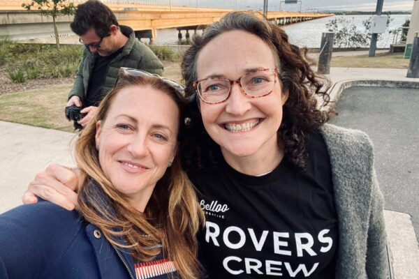 Two women smile at the camera. One has an arm draped arounf the others' shoulder. They are standing in front of a beach. One wears a tee shirt reading 'Rovers Crew'