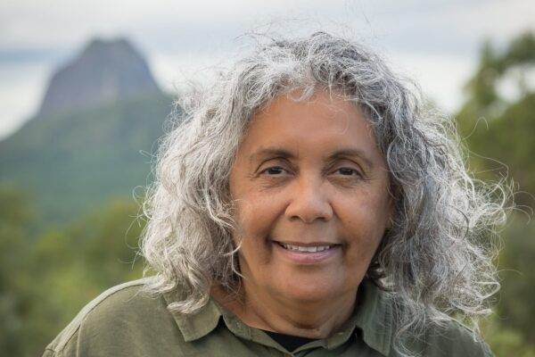 Roxanne McDonald, an indigenouse woman in her mid-fifties smiles at the camera. she is standing in front of a mountain range. Her hair is grey and wild and she is smiling.