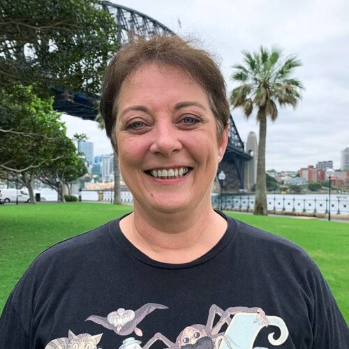 A woman in a black tee shirt featuring a graphic of Alice in Wonderland characters, stands in front of a background of grass, trees and the harbour bridge. She has short hair and is smiling direct to camera.