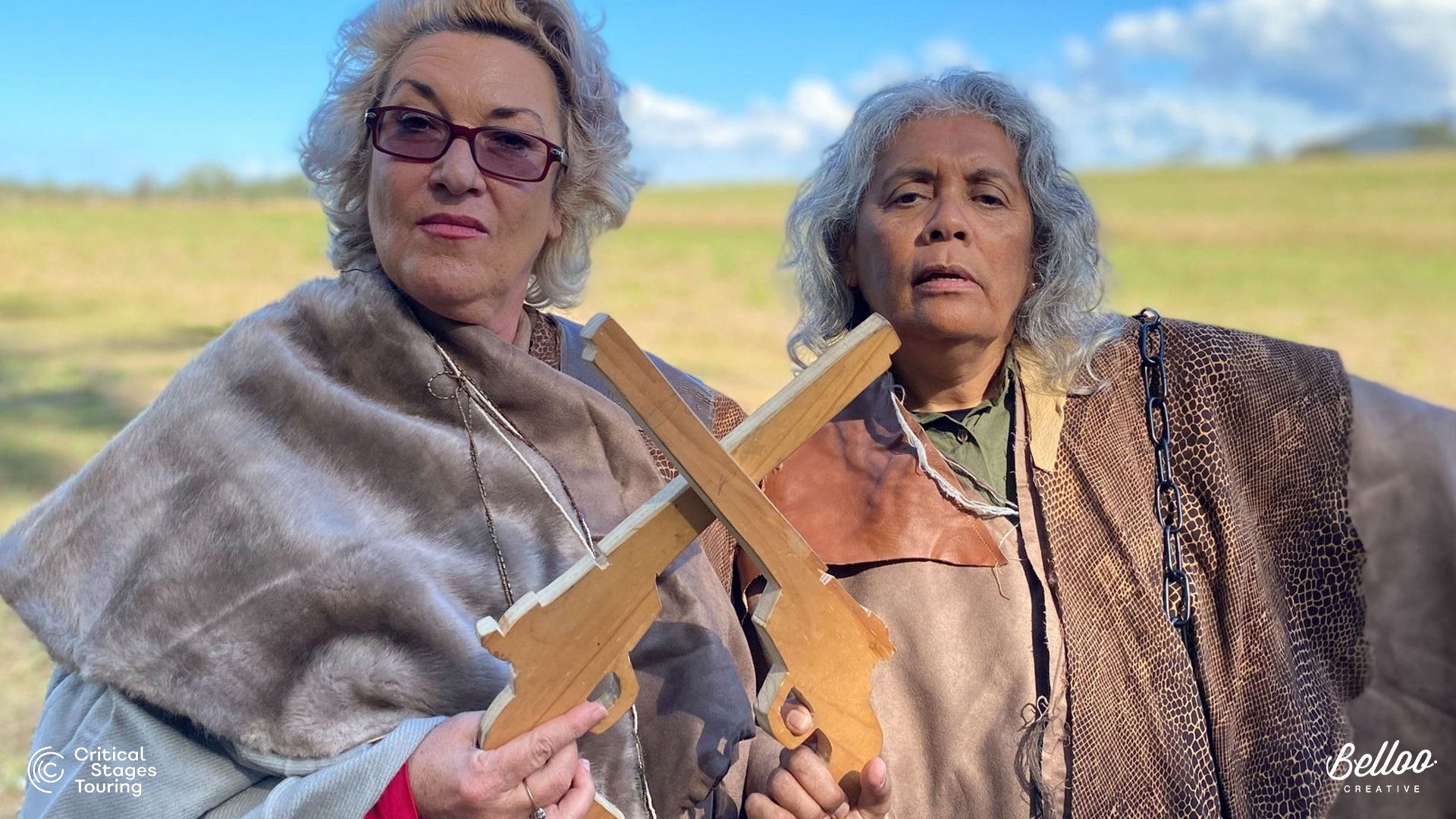 Two women in their mid-50's wear fur shawls and hold timber cut-outs of pistols across themselves. They look determined and brave.