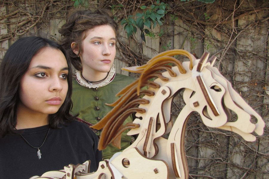Two young women stand side-by-sdie holding a small mechanical horse made from timber. One girl looks modern wearing a black tee-shirt, the other is dressed in Victorian costume.