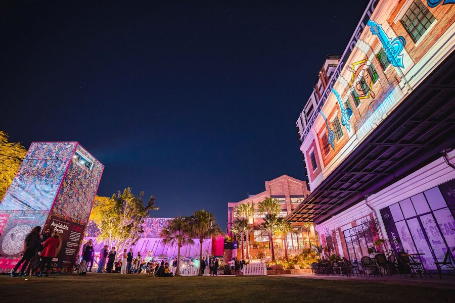 We look up from the centre ofa street looking up the buildings that line the strip - all illuminated by graphics and animations
